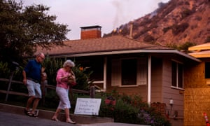 People walk past a sign thanking firefighters and first responders as they return home, as smoke from the Bobcat Fire burning in the San Gabriel mountains rises above, in Monrovia, California, last week.
