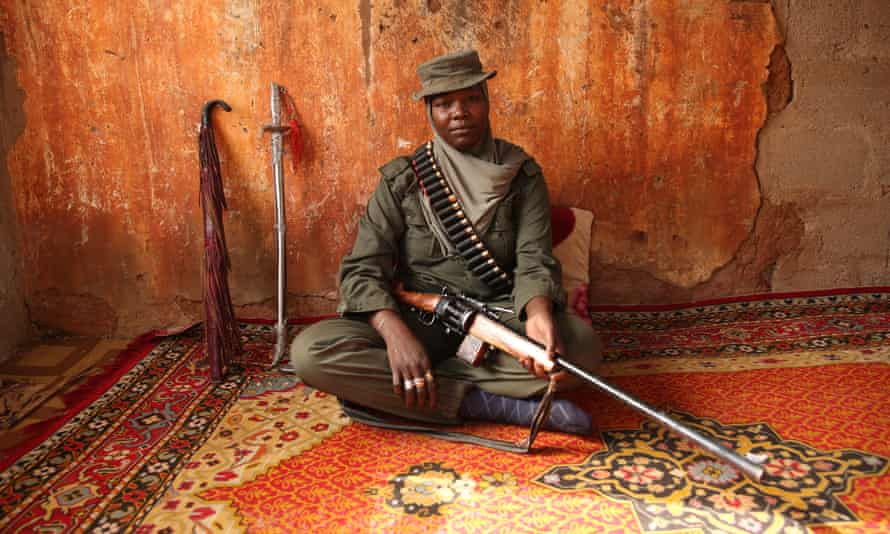Aisha Gombi Bakari sits with her rifle.