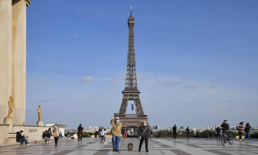 People are seen standing near the Eiffel Tower in Paris, France.