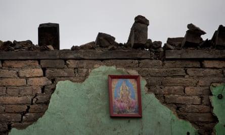 A portrait of Hindu goddess Lakshmi hangs on the remains of a house in Kathmandu