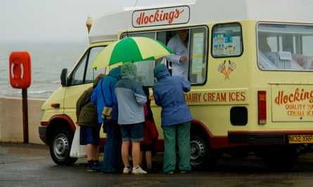 People in the rain, with an umbrella, ordering from an ice-cream van on a seafront.