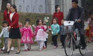 Children walk with decorative flowers for the upcoming anniversary celebrations in Pyongyang.