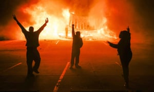 Protestors parade in the parking lot of a burning auto parts store in Ferguson