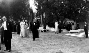 Opera goers during an interval at the opening of the first Glyndebourne season, 1934. Pieces of scenery are lying on the lawn.