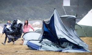 Festivalgoers pass a collapsed tent at Lulworth Castle in Dorset during Camp Bestival.