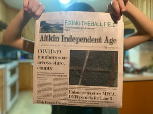 Amasa Kloecker, 8, holds up a newspaper with headlines about Covid-19 cases and construction beginning on a northern Minnesota pipeline.