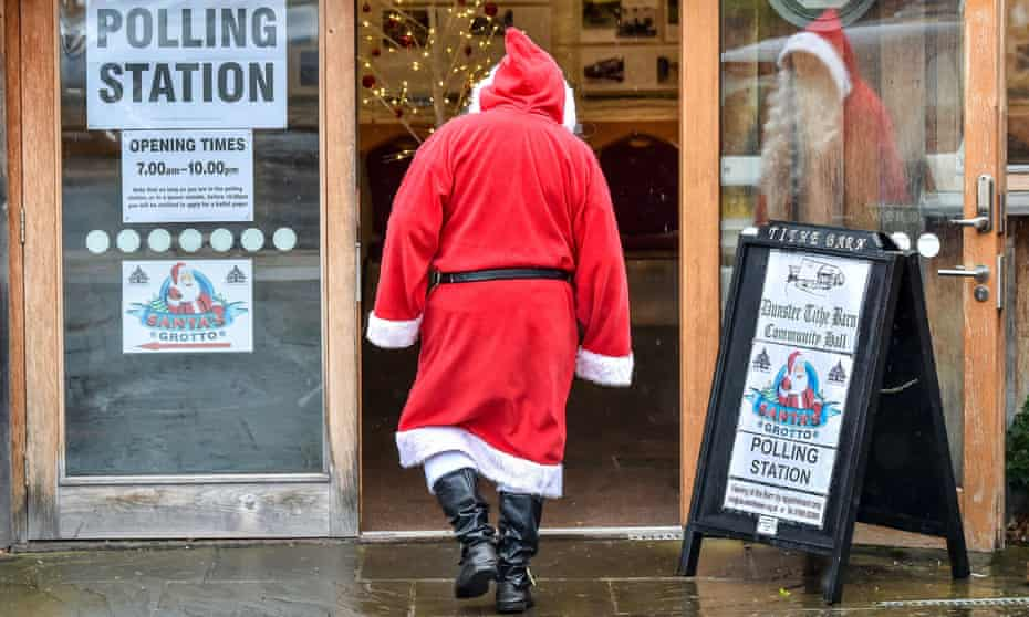 A man dressed as Father Christmas enters his grotto at the Dunster Tithe Barn near Minehead, Somerset, which is being used as a polling station