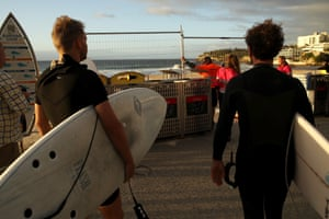 Surfers look on as the barrier fence is opened