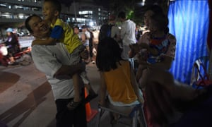 People react near a hospital, where the children's football team members are being treated.