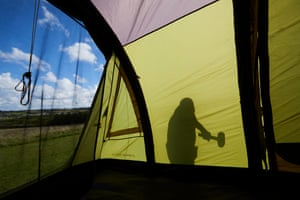 Forty year camping veteran Mick Cooper from Sheffield erecting his inflatable tent shortly after arriving on the site.