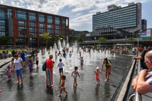 People splash in the fountains in Piccadilly Gardens in central Manchester.