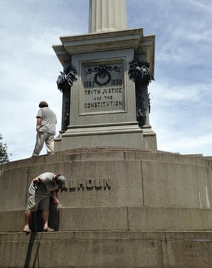"Workmen remove graffiti from a statue of John C Calhoun in Charleston after it was painted with the words '""racist'"" and '""slavery'"