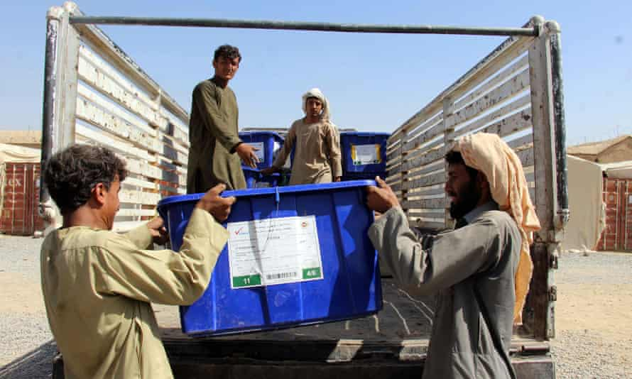 Workers transport ballot boxes and electoral material to polling stations in Kandahar