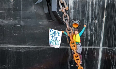A woman identified as Chiara D''Angelo has suspended herself in a climbing harness from the anchor chain of the Royal Dutch Shell support ship Arctic Challenger in the harbor at Bellingham, Washington.