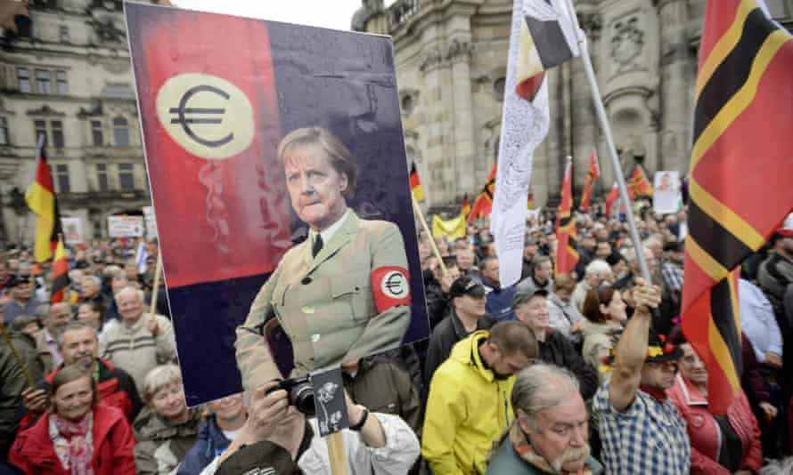 Pegida supporters hold up a poster showing Chancellor Angela Merkel in a uniform with an euro armband at a rally in Dresden on 1 June 2015.