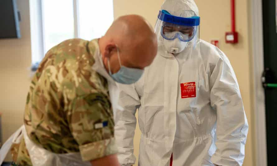 Members of the British army learn how to apply PPE during training to support the Welsh Ambulance Service NHS Trust.