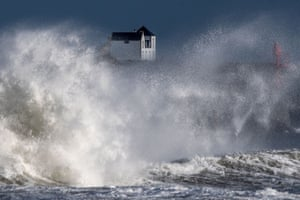 A big wave crashes on a pier in front of a house in western France as storm Bella caused torrential rain and heavy winds in much of France