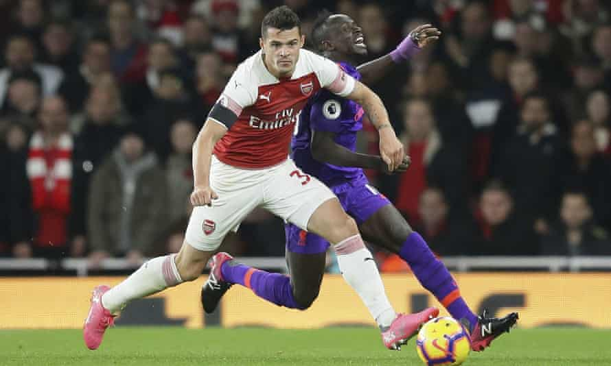 Arsenal's Granit Xhaka fights for the ball with Liverpool's Sadio Mané.