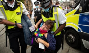 Police officers detain an an Extinction Rebellion activist during a rally in Parliament Square, London.
