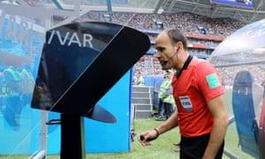 Referee Antonio Mateu reviews the VAR footage before awarding Australia a penalty against Denmark