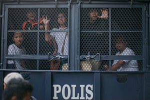 Malaysian protesters are held inside a police vehicle during protests against prime minister Najib Razak, calling on him to step down.