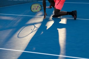 A player crouches down in the afternoon sunlight during a doubles match.