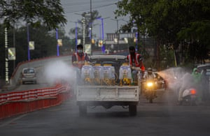 On a street in Gauhati, municipal workers spray disinfectant as a preventive measure