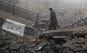 An elderly woman in Donetsk, Ukraine, walks across a bridge destroyed by heavy fighting