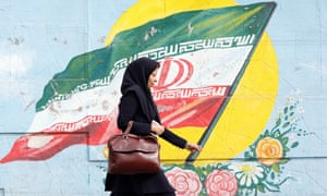 An Iranian woman walks past a mural depicting Iran's national flag in Tehran.