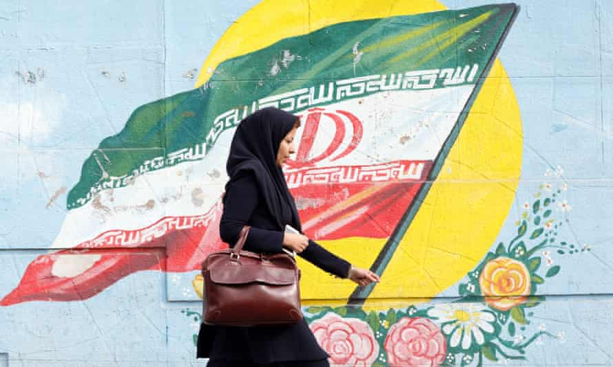 An Iranian woman walks past a mural depicting Iran's national flag in Tehran.