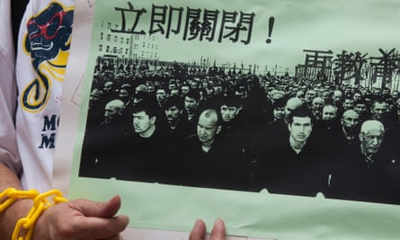 A protester in Hong Kong holds a photo of Uighur prisoners.