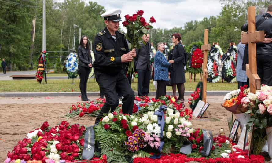 A serviceman lays flowers at a grave in St Petersburg, Russia