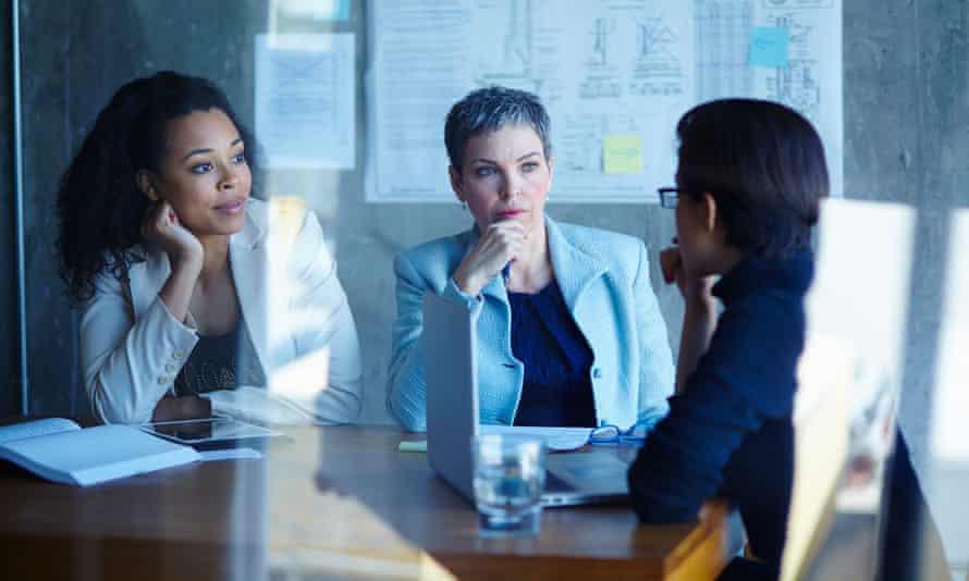 Three businesswomen discussing ideas in boardroom