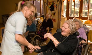 Member of care staff sharing joke with elderly resident at a care home, Isleworth, Middlesex