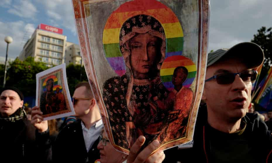 People hold pictures of the 'Black Madonna of Czestochowa' with a rainbow-coloured halo at a protest in Warsaw.
