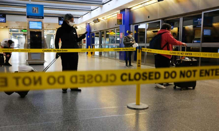 Travelers walk through a mostly empty John F Kennedy airport in New York.