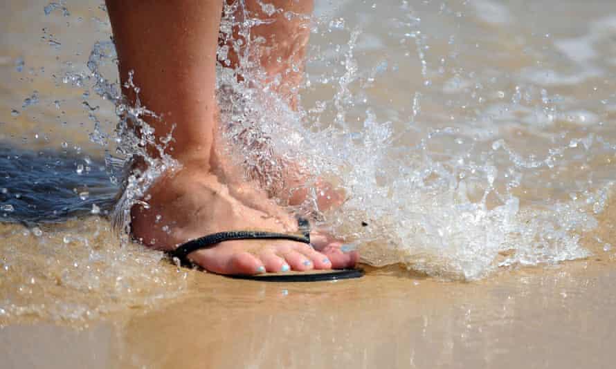 Feet in flip-flops splashing in water on beach