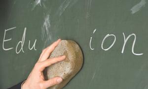A teacher cleans a blackboard