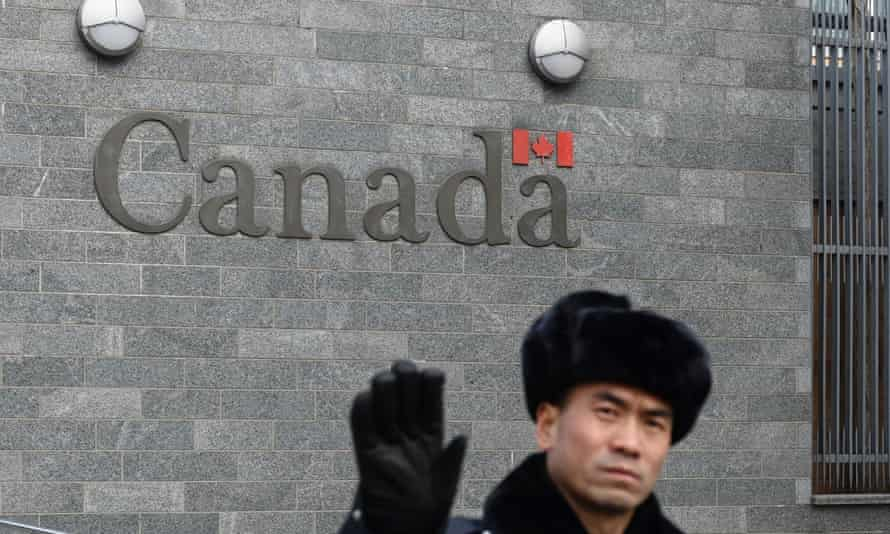 A guard tries to block photos from being taken outside the Canadian embassy in Beijing. Sino-Canadian tie are increasingly fraught.