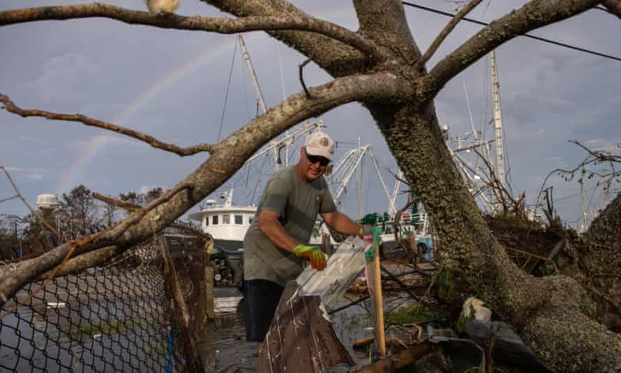 A man clears debris from his yard in the aftermath of Hurricane Ida in Galliano, Louisiana