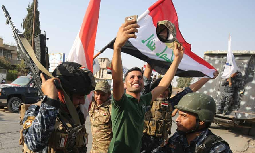 An Iraqi man takes a selfie with federal police officers as they celebrate the 'liberation' of Mosul from Islamic State.