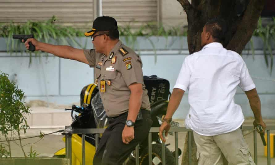 An Indonesian policeman fires his handgun towards suspects outside a cafe after a series of blasts hit the Indonesia capital Jakarta.