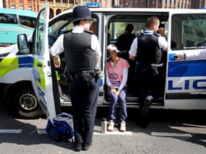 A demonstrator sits in a police car after being arrested on Waterloo Bridge