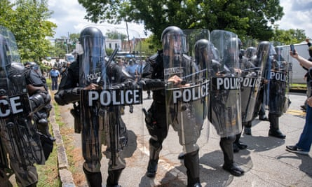 Riot police move protesters after confrontations between protesters and militia members in Stone Mountain, Georgia.