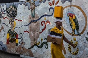 A woman passes one of the few open squares in the slum community of Jalousie – this mural was supervised by the Haitian painter and sculptor Patrick Vilaire and was inspired by one of his works