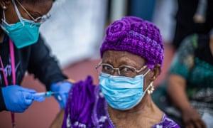 Ebony Thomas, a nurse, administers a Covid-19 vaccine to Cecilia Onwytalu, 89, at Kedren community health center, in South Central Los Angeles.