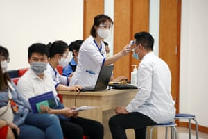 A health worker (R) has his temperature checked after receiving a shot of the AstraZeneca Covid-19 vaccine in Hanoi, Vietnam, on 17 March.