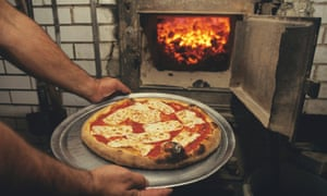 A staff member holds a margherita pizza on a tray in front of the open coal-fired oven at Lombardi's pizzeria in New York. US.