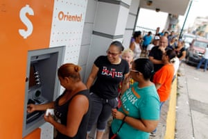 People queue in line to withdraw money from an ATM in Cataño
