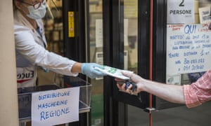 Pharmacists distribute free protective masks in a bid to combat the spread of Covid-19 in Bologna, Italy.